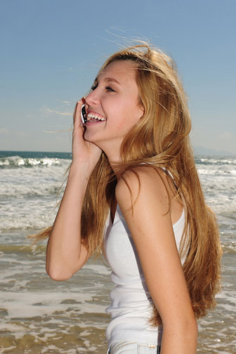 young woman making a long distance phone call from a beach